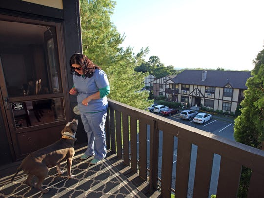 Maryann Boyd with her dog, Bailey, on the balcony of her Valley Cottage condo.