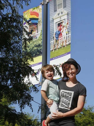 """Autumn Bland holds her son, Fox Hudson, 2, and stands Thursday in front of two of the """"Portraits of Pride"""" series of photographs she has taken that have been made into banners. These banners hang on West Market Street in Akron's Highland Square neighborhood. Other banners hang in Highland Square, as well as the city's Wallhaven area.  Bland is pictured on Aug. 20, 2020 in Akron, Ohio. Community AIDS Network/Akron Pride Initiative (CANAPI) reached out to Bland to photograph the LGBTQ+ people and families in Akron. In the photographs are Jared and his mother Dorene, left, and Nick and Steve with their son Anderson, 2."""