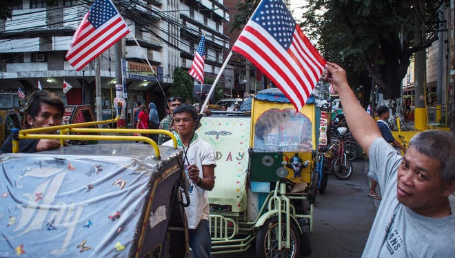 Bicycle taxis in Manila show off American flags on Sunday on the eve of a visit by President Obama.