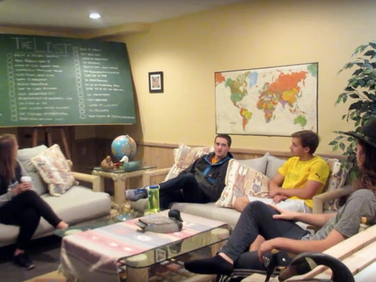 Rachel (from left), Kevin Reardon, Owen Gibson and Gregory Smith sit in Smith's basement with the bucket list they developed to tackle this past summer.