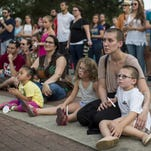 Participants gather Saturday at Parc Sans Souci for a candlelight vigil for victims of the Grand 16 Theatre Shooting.