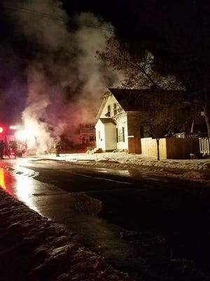 Firefighters and police on the scene of a house fire on South Cedar Avenue Tuesday morning.