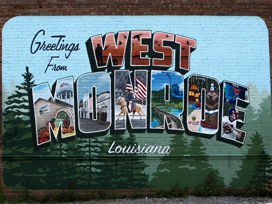 """A postcard mural that reads """"Greetings from West Monroe"""" is painted on the side of the building where Miss Kay's Sweets & Eats is located on Antique Alley in West Monroe, Wednesday, July 5, 2017."""