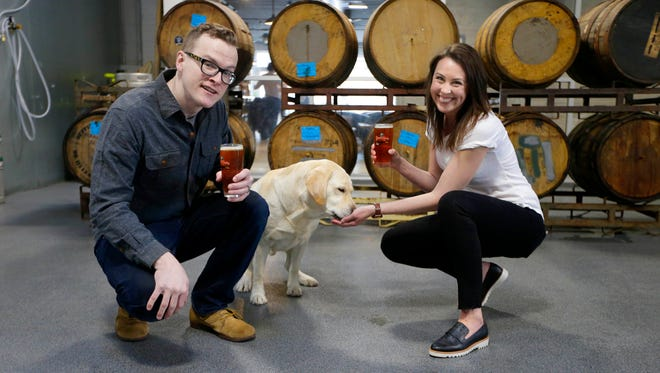 Nikki Collier gives her dog, Tonka, a 5-year-old yellow Labador, a Leashless Lab dog treat at Black Husky Brewery in Riverwest. Collier initially used spent grain from beer made by her husband, Kevin Goss. Now she gets it from local breweries, including Black Husky.