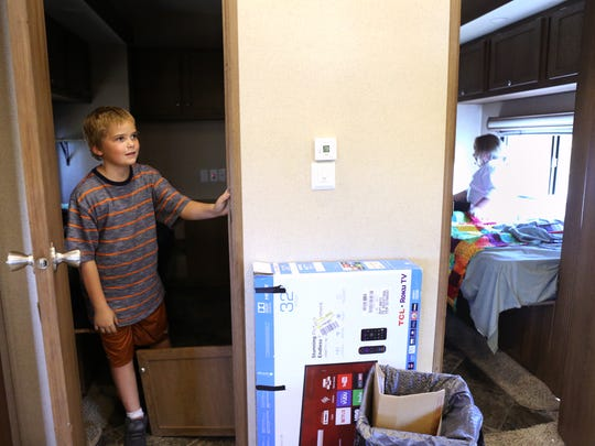 Blu McGrady, 8, stashes his soft drink in the room he shares with his brother before going to skateboard in his family's new home on Tuesday, Oct. 24, 2017. His family was the recipient of RV through the Homes for Displaced Marlins program.
