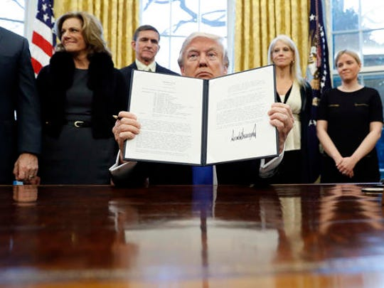 "FILE - In this Saturday, Jan. 28, 2017 file photo, President Donald Trump holds up a signed Presidential Memorandum in the Oval Office in Washington. The document directs his administration to ""develop a comprehensive plan to defeat ISIS."""