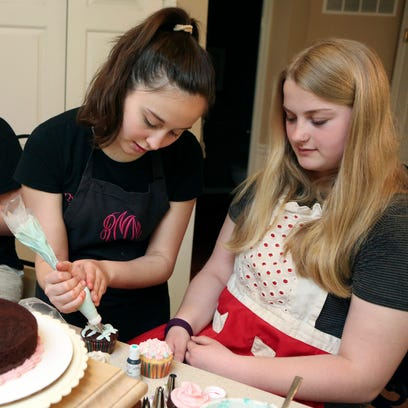High schooler Ryan MacEachern shows Meadow Wilson, 11, of Rising Sun, Md., how to create fondant details as she conducts a lesson in cake and cupcake decorating at her family's Northeast, Md., home.