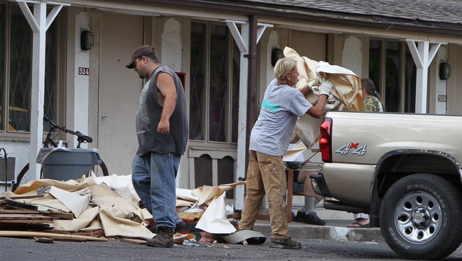 Workers load debris from a room at Florence Inn into a pick-up truck.