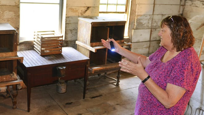 Sarah Lutze shows artifacts that will be on display Saturday during the housebarn's open house event.
