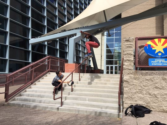 """Eric Decker films Eric Johnson as he attempts a skateboard trick off the railing at Phoenix Symphony Hall on Friday, May 22, 2015. """"Usually it's a heck of a lot hotter,"""" Decker said."""