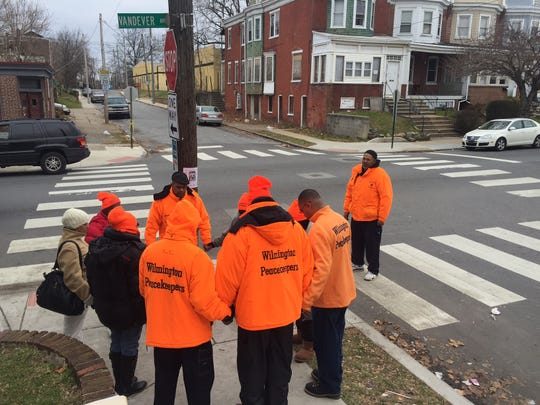 Members of the Wilmington PeaceKeepers, an anti-violence group that travels around the city, prayed the morning of Dec. 20, near where Derrick Caudle, 43, fatally was fatally the night before. City police on Wednesday announced the arrest of a suspect, charged with first-degree murder in Caudle's killing.
