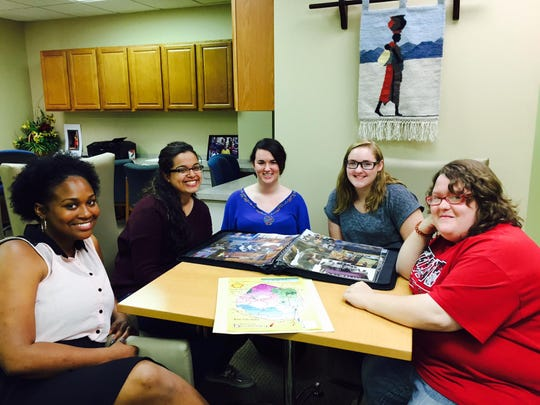 Jazmyn Herring (from left), Amanda Neves, Jordyn Price, Emily Perry and Chelsie Pierce Kennedy checked out photos from their trip to Swaziland.