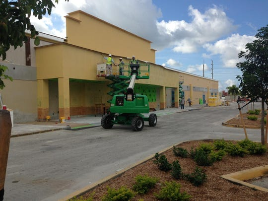 Workers remodel the exterior of the old Kmart plaza on Cleveland Avenue in Fort Myers. The Kmart will be replaced with a Floor & Decor.
