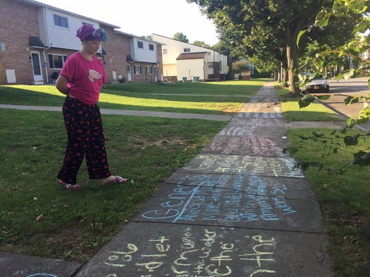 Chelsea Pike, 14, admires the sidewalk art she and