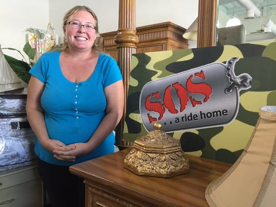 Erica Stone, founder of SOS, stands next to one of the many items that will soon be for sale at the organization's resale boutique and veterans communication center.