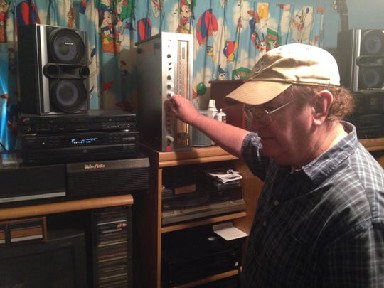"""Danny White tinkers with some of his equipment at his home studio, where he has been working on a new album, """"A Good Country Song."""""""