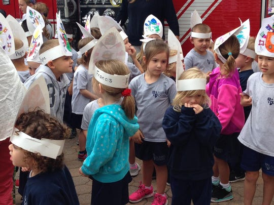 Students from All Saints Catholic School in Elsmere, who walked around town singing songs in advance of Pope Francis visiting Philadelphia, decorated their own pope hats or mitres.