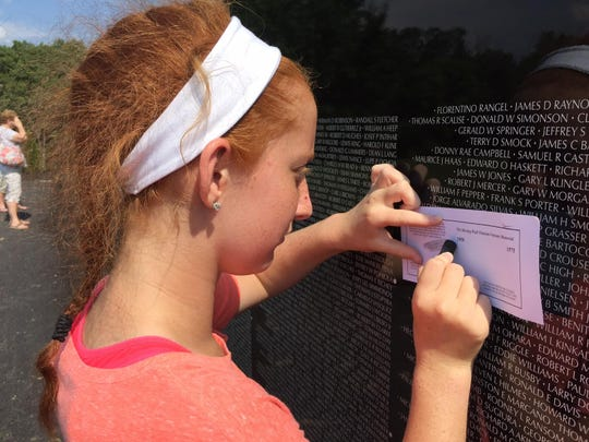 Maria Sprecker, 15, of Erlanger, traces a name from The Moving Wall Vietnam Veterans Memorial.
