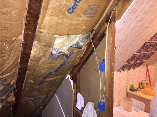 Insulation is exposed in this wall of an upper floor of a rooming house on West End Avenue in Somerville.