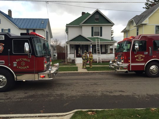 Firefighters stand outside 322 W. Charles St. in Bucyrus