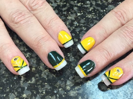 Acrylic nails get the green and gold treatment from owner Melissa Strehlow at Options Hair Team in Ashwaubenon.
