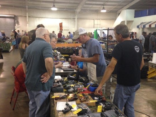 Justin Tull, owner of T&T Sporting Goods, shows a gun to customers at the R.K. Gun and Knife Show Sunday.