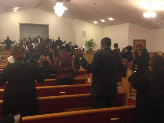 The New Greater Bethel CME Church members, all dressed in black, bow their heads for prayer Sunday morning. Members of African-American churches across the country dressed in all black on Sunday to protest police violence.