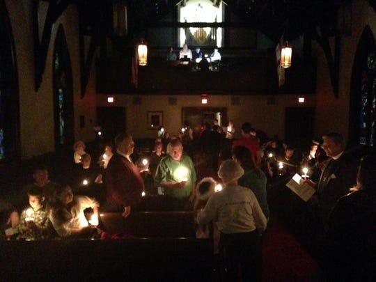 Church-goers, one by one, get their candle lit Sunday night at St. Luke's Episcopal Church's Feast of Lights.