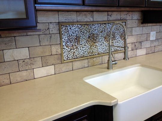 Casey Minton with USA Stone and Tile designed this backsplash using a combination of natural stone and glass. The surrounding stone tiles were purchased from Triton Stone of Nashville, and the central design came from Sydney Glass Distributors.
