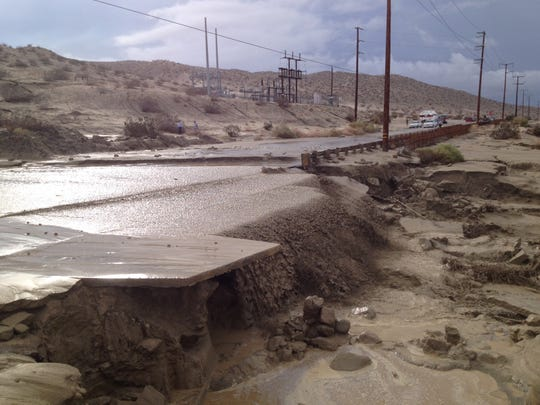 Flooding washes away the ground alongside Varner Road on Monday.