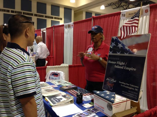 Marva X, of Honor Flight, Inland Empire, talks to a young serviceman and his wife during the 5th Annual Veterans Expo in the Fullenwider Auditorium at the Riverside County Fairgrounds in Indio on Saturday, Oct. 11, 2014.