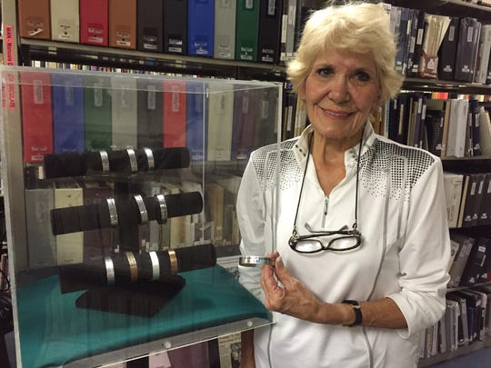 Monnie Lutz stands near a case holding POW/MIA bracelets donated to the Palm Springs Air Museum. Lutz donated a POW/MIA bracelet bearing the name of Lt. Col. Robert Sawhill Jr. to the museum on Monday.