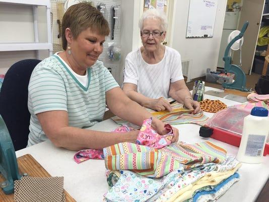 volunteers sew bibs