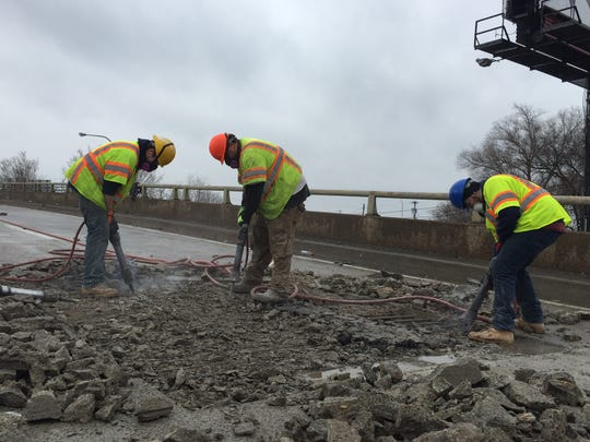 Workers repair potholes on the Del. 141 bridge Thursday afternoon.