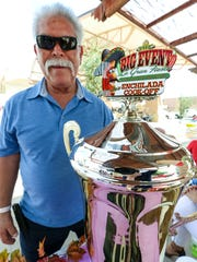 Roberto Estrada stands next to the Roberto's Enchilada Cook-Off trophy on Sunday during the third day of The Big Event at the Plaza de Las Cruces.