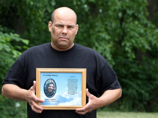 Keith Malave of Keansburg holds a photo of his 18-year-old son, Joseph, who died in February. The family is battling with the Keansburg School District.