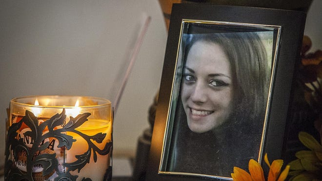 A candle burns next to a photo of Brianna DiBattiste in the home of her mother, Julie Hunt, in October 2014, days after DNA tests had confirmed that remains found in a rural area of Jay County on Sept. 1, 2014, were DiBattiste's.