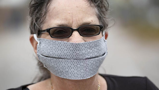 Debra Shaw, Lake Worth, wears a homemade mask a friend made for her as she enters Walmart in Royal Palm Beach, Monday, April 13, 2020.