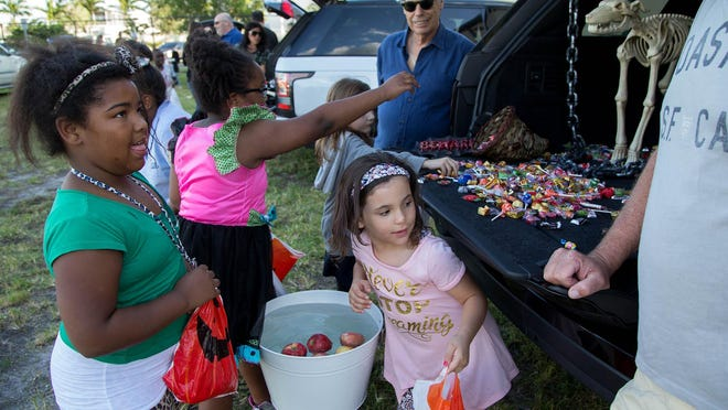 Neil S. Hirsch (background) watches children take part in the Trunk or Treat event at Boys & Girls Club of Wellington in 2017.