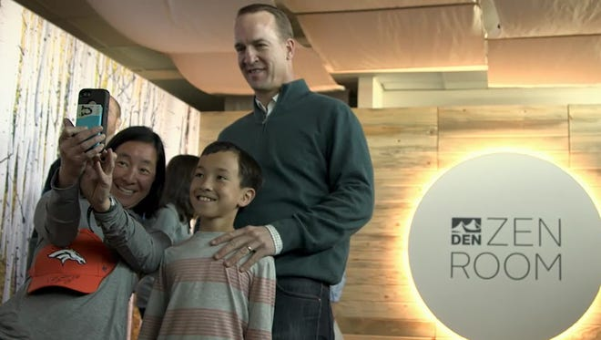 After surprising travelers at Denver International Airport, former Broncos quarterback Peyton Manning takes selfies, signs autographs and gives a few hugs and handshakes.