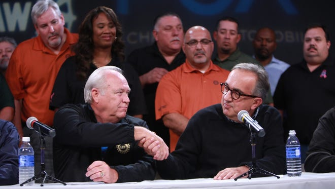 UAW President Dennis Williams and FCA CEO Sergio Marchionne shake hands while speaking during a press conference in the auditorium of the UAW-Chrysler NTC Building in Detroit after the UAW announced Tuesday that it has reached a tentative agreement with FCA US LLC.