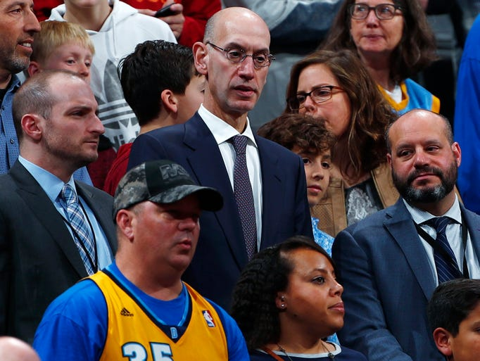 NBA commissioner Adam Silver, center, marvels at the