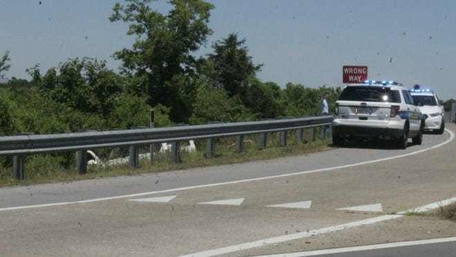 Detectives comb the white pickup truck driven by the alleged bank robber where it was stopped at an Exit 89 off ramp.