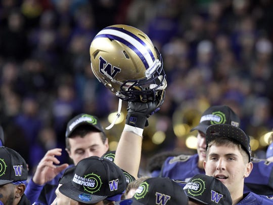 Washington players celebrate after defeating Colorado in the Pac-12 championship, but the Huskies will face a much more difficult task Saturday against Alabama in the Peach Bowl, as they are a two-touchdown underdog.