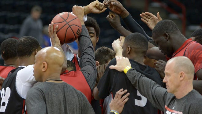 The Bearcats huddle during practice Wednesday in Spokane.