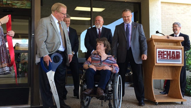 Lee Pfuger, left, with scissor in hand, stands next to Hayley Perrine shortly after cutting the ribbon Thursday to mark the grand reveal of renovations at San Angelo's West Texas Rehabilitation Center. The pair participated in the original ribbon-cutting when the center opened 35 years ago.