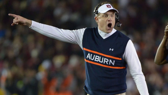 As if pointing the way, Auburn coach Gus Malzahn directs his team Monday during the first half of the BCS National Championship Game in Pasadena, Calif.
