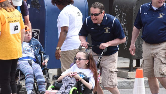 Tom O'Neil, assistant principal at Beacon High School, pushes Jadelyn Panko's wheelchair during the Think Differently Dash in 2017.