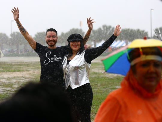 Manuel Barrera (left) and Camille Cruz get their photo taken as they stand in the rain during the second day of Fiesta de la Flor: A celebration of the Life & Legacy of Selena on Saturday, April 18, 2015, at North Bayfront Park in Corpus Christi.
