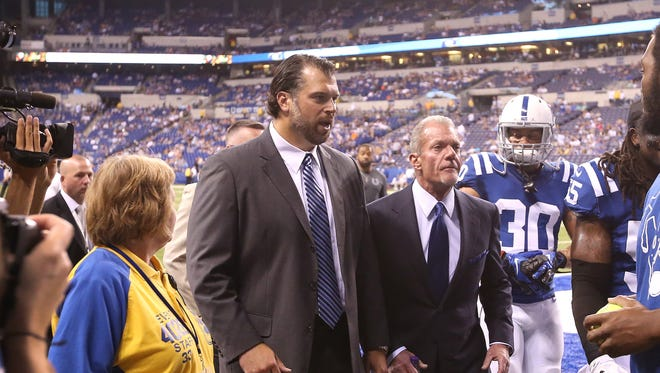 Colts general manager Ryan Grigson and owner Jim Irsay talk as they walk off the field with the team before kickoff against the Saints.  Indianapolis hosted New Orleans in their third preseason game of the year Saturday, August 23, 2014 at Lucas Oil Stadium.
